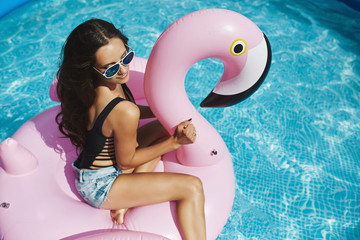 Fashionable brunette model woman with sexy perfect body in stylish black bikini and in glamorous sunglasses posing on an inflatable pink flamingo at the swimming pool outdoors