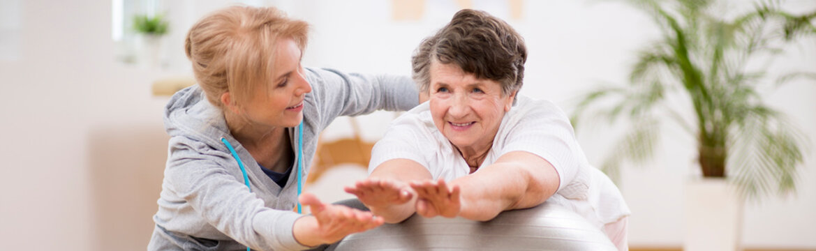 Panorama capture of pilates instructor helping senior woman to stretch on the exercising ball