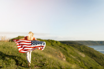 Beautiful woman holding American Flag. Patriotic holiday.