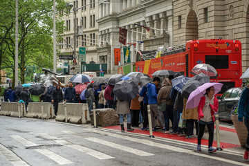 People line up to have their photo taken by the charging bull statue in the Manhattan borough of New York