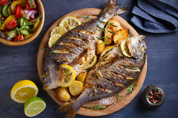 Roasted fish and potatoes, served on wooden tray. overhead, horizontal - image