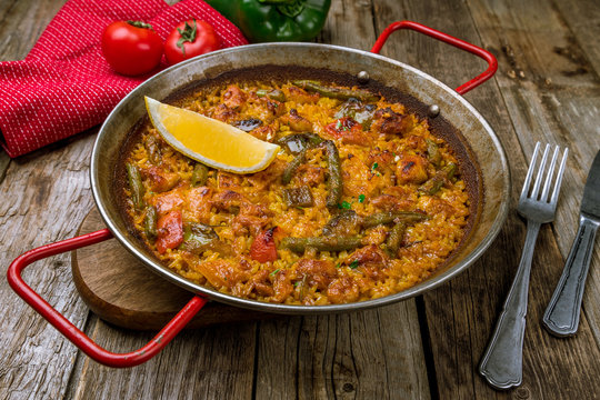 paella with chicken on wooden background