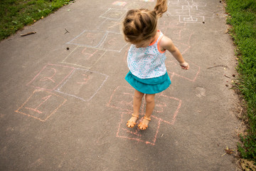 A toddler aged girl playing hopscotch outside in a park.