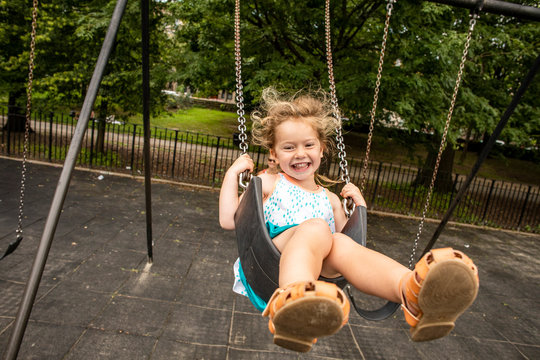 A toddler aged girl swinging and having fun outdoors at a park with her mother.