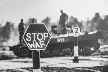 Creative Badge - Stop Wars. Concept - no war, stop military operations, world peace. Stop war sign on the background of military equipment.