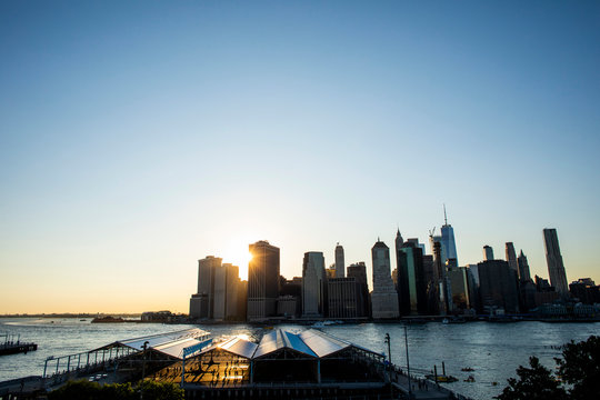 A cityscape of downtown Manhattan at sunset with a sunflare in the background.