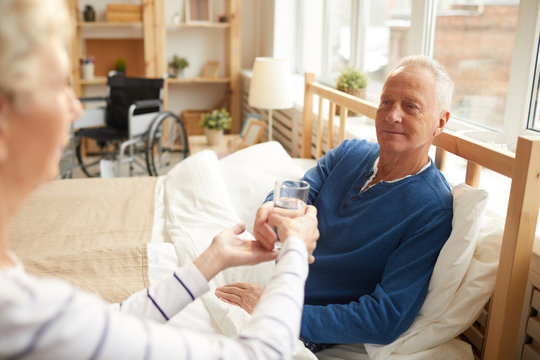 Portrait of white haired senior man lying on bed and taking glass of water handed by wife, copy space