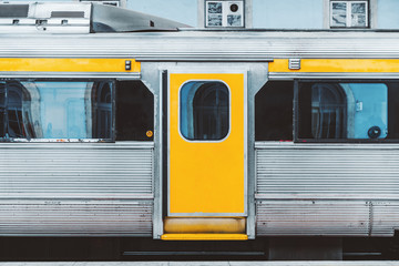 Aluminium Prints Delhi A typical European suburban train waiting on the platform in Portugal; the area of the door in the middle of the wagon of an old-fashioned high-speed train with aluminum plating with yellow areas