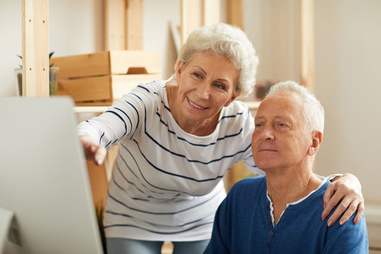 Portrait of modern senior couple using computer in sunlit apartment doing online shopping, copy space