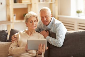 Portrait of modern senior couple using digital tablet  at home lit by sunlight, copy space