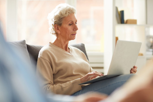 Warm toned portrait of contemporary mature woman using laptop sitting on sofa at home, copy space