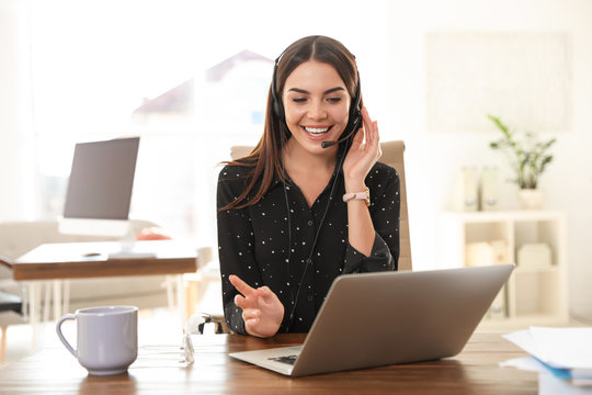 Young woman using video chat on laptop in home office
