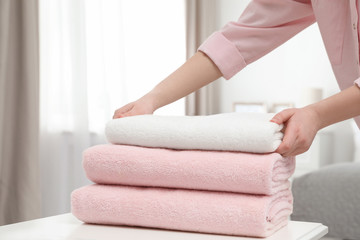 Woman stacking clean towels on table in room