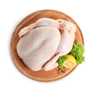 Wooden board with raw turkey and ingredients on white background, top view