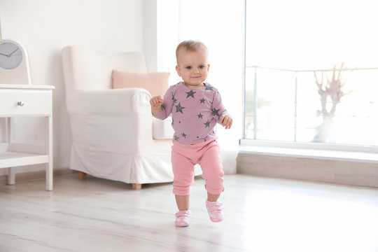 Cute baby girl walking in room at home