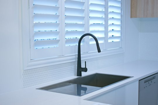 Open plantation shutters and black kitchen sink mixer tap.