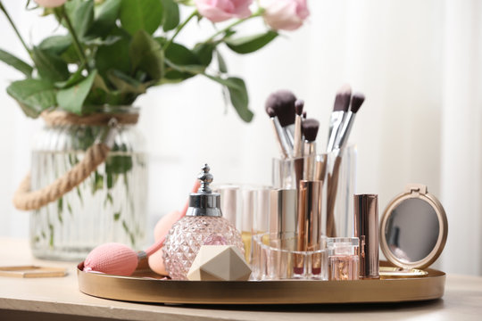 Tray with different makeup products and accessories on dressing table