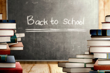 Close up view of pile of books on wooden table and blackboard with Back to School message