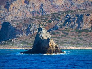 Small stony island - waves crashing - big rocky cliffs in the background - deep blue sea