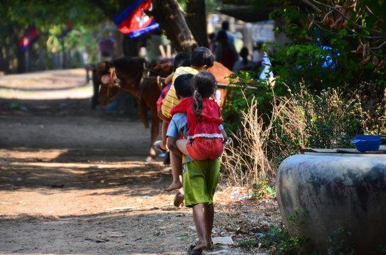 カンボジアのクラチェ メコン川沿いの村 大きな子供が小さな子供をおんぶする姿 路上に佇む馬