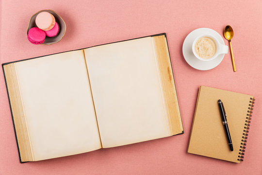 Empty ancient book open with pink french macarons on the side, coffee cup, golden spoon and notebook with pen over a pink tablecloth background.