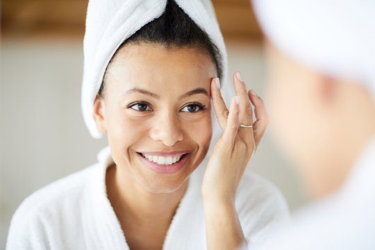 Head and shoulders portrait of  smiling Mixed-Race woman applying face cream during morning routine, copy space