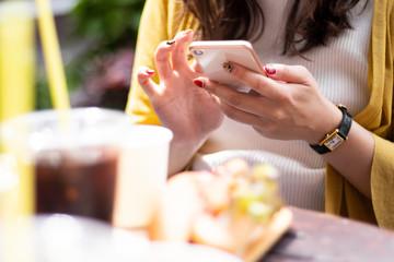 食事時にスマートフォンを操作する女性