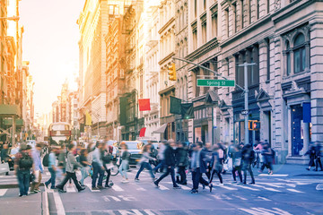 Diverse groups of people walk across the crowded intersection of Broadway and Spring Street in the SoHo neighborhood of Manhattan in New York City