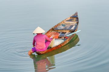 Unusual view of Vietnamese woman checking her fishing net. Hoian