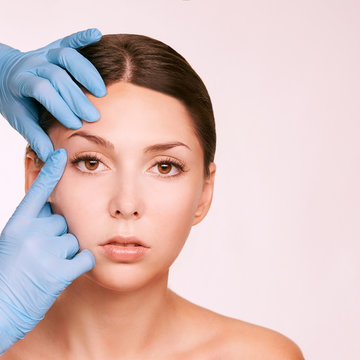 Female derma rejuvenate treatment. Doctor in gloves touch woman face. Cosmetology pretty portrait. Facial injection patient
