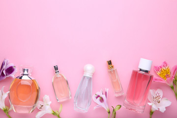 Perfume bottles with flowers on pink background, copy space