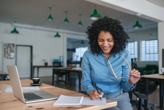 Smiling businesswoman sitting at work writing ideas in a notebook