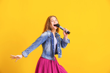 Teenage girl with microphone singing against color background Fotobehang