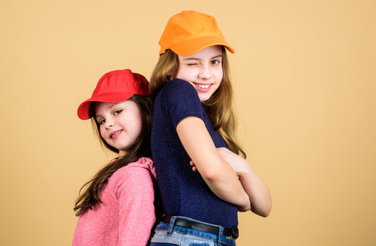 Cool girls. Sisters stand back to back beige background. Little cute girls wearing bright baseball caps. Modern fashion. Hats and caps. Stylish accessory. Kids fashion. Feeling confident wearing caps