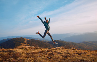 Happy woman hiker jumping on mountain ridge on blue cloudy sky and mountains background. Travel and active lifestyle concept.