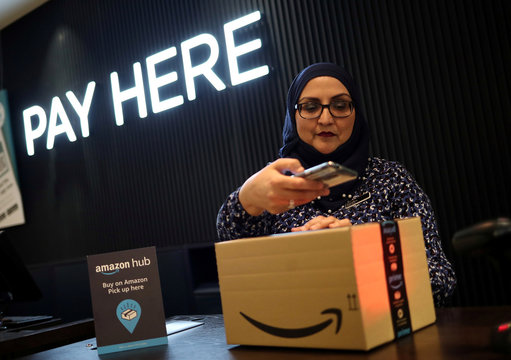 An employee demonstrates Amazon Counter, a click and collect service allowing customers to collect their Amazon parcels in-store at a Next store in London