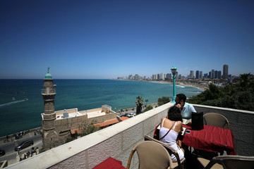 A couple look at the Mediterranean Sea as Tel Aviv's skyline is seen in the background, from a restaurant in Jaffa, Israel