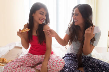 Two smiling young girls sitting on bed at home eating pizza and having fun