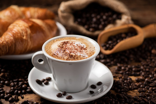 A cup of cappuccino with coffee bean as background.