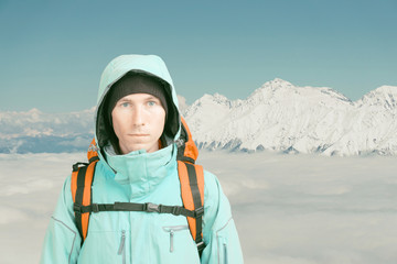 Young male mountain climber on winter mountain top view looking at camera. Front view. Active lifestyle in cold weather. Winter mountain landscape and cloudy sky. Active lifestyle and tourism.