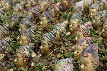 A collection of near identical female Buddhist figurines lined up in rows forms a pattern with  natural plant growth occurring in between the gaps.