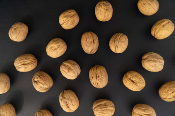 Walnuts in the shell scattered on black surface, top view. Background of round walnuts. Healthy nuts and seeds background.