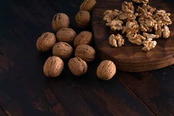 Cracked and whole walnuts lying on cutting board and wooden black table, side view. Healthy nuts and seeds composition.