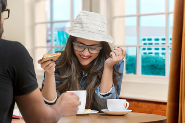 Smiling teenage girl wearing spectacles and hat sitting at restaurant table with friend eating pizza