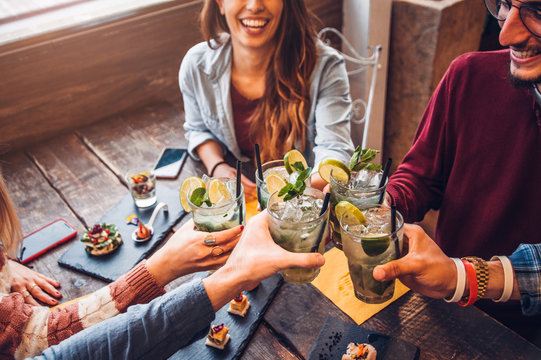 Happy friends drinking mojito at bar restaurant. Concept about young people having fun