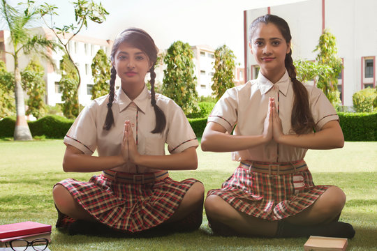 School girls meditating with books kept aside them in the school campus garden