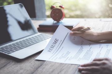 Business man review his resume application on desk, laptop computer, job seeker