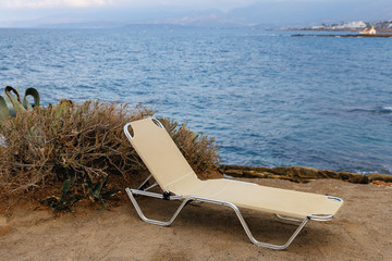 new lonely chaise lounge on the sandy beach of the Greek resort of Hersonissos against the blue sea