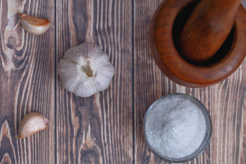 head, a few cloves of garlic, salt and mortar on a wooden background