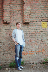 young 30s age man  in white and blue casual clothing standing with his hands in pockets in full size near old red brick wall background, urban lifestyle stock photo image
